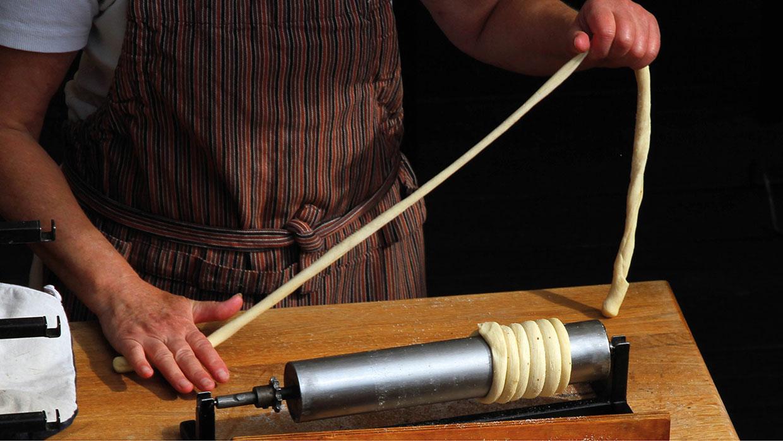 Baumstriezel Teig-Streifen um die Rolle wickeln und danach in Zucker wälzen